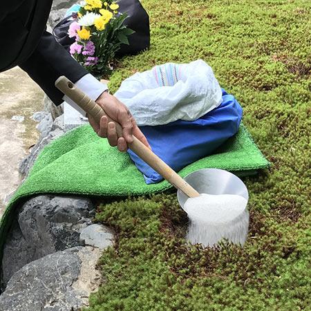 樹木葬の納骨のケイ砂をかけるシーン